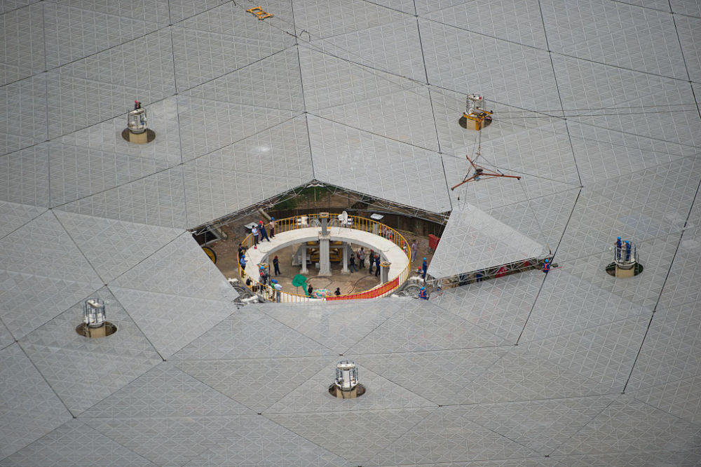 PINGTANG, CHINA - JULY 03: Workers install the last panel into the center of a Five-hundred-meter Aperture Spherical Telescope (FAST) on July 3, 2016 in Pingtang, Guizhou Province of China. The dish-like telescope, as large as 30 football fields, costing 1.2 billion yuan (about 180 million USD), will be used for reasearch and further adjustment according to China Daily. (Photo by Dai Chuanfu/VCG)***_***